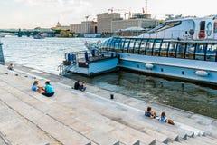 Leute auf Pushkin-Damm von Park Moskaus Gorky und von Freizeitboot im Fluss Stockfoto