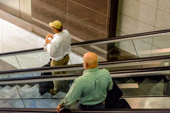 Leute auf Rolltreppen an einem Flughafen Stockfotografie