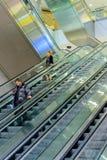 Leute auf Rolltreppen an einem Flughafen Stockfotos