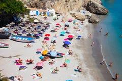 Leute auf sonnigem Strand und im Meer stockfoto