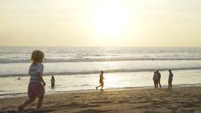 Leute auf Strand bei Sonnenuntergang in Bali Betrieb des kleinen Jungen stock footage