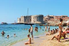 Leute auf Strand an der adriatisches See- und Dubrovnik-Festung Stockfotos