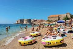 Leute auf Strand im adriatisches See- und Dubrovnik-Fort Stockfotos