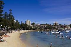 Leute auf Strand mit Stadt auf Hintergrund Lizenzfreies Stockbild