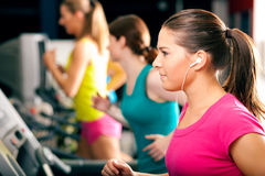 Leute auf Tretmühle im Gymnastikbetrieb Stockfoto