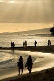 Leute auf Waikiki-Strand bei Sonnenuntergang Stockfotos