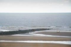 Leute auf Wellenbrecher stockfotos