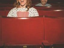 Leute-aufpassender Film im Kino Stockbilder