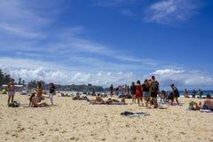 Leute am australischen Strand mit Stadt auf dem Hintergrund Stockfoto