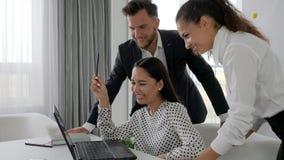 Leute bei der Arbeit, die Manager nähern sich Laptopschirm sprechend mit einander, kreative Arbeitskräfte stock video