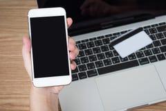 Leute benutzen Smartphones, um ?ber eine Kreditkarte zu zahlen, die auf einen Laptop auf einem Holztisch gesetzt wird Feder, Bril stockfoto