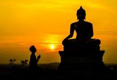 Leute beten Buddha, Buddha-Statue auf Sonnenunterganghimmelhintergrund an Lizenzfreies Stockbild