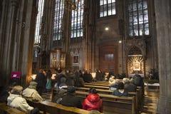 Leute beten und beleuchten Kerzen Stockbild