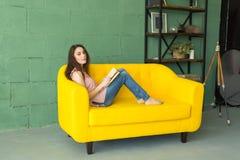 Leute, Bildung und Innenkonzept - junge Frau, die auf einem Sofa liegt und ein Buch liest stockfoto