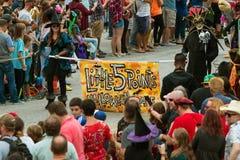 Leute Carry Banner To Start Little fünf Punkte Halloween-Parade- Stockbilder