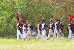 Leute in den historischen Kostümen marschieren auf das Schlachtfeld Lizenzfreies Stockfoto