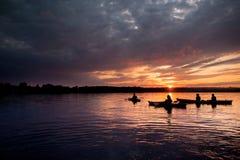 Leute in den Kajaks auf dem Fluss auf dem szenischen Sonnenuntergang stockbild