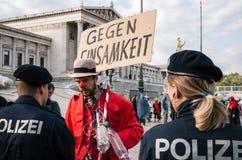 Leute in den Kostümen von Pantomimen und von Clownen protestieren gegen österreichisches Verbot auf Plätzen des Vollgesichtsschle Stockbild