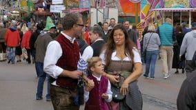 Leute in den nationalen bayerischen Klagen gehend entlang die Straße von Oktoberfest-Festival Bayern, Deutschland stock video footage