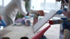 Leute in den Schutzblechen Behandschuhte H?nde Roter Lack Art Studio zusammenarbeit stock video