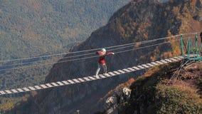Leute in den Sturzhelmen gehend entlang Brücke des hängenden Seils über Abgrund stock video
