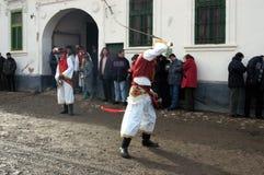 Leute in den traditionellen Kostümen den Winterkarneval feiernd Lizenzfreie Stockbilder