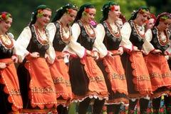 Leute in den traditionellen Kostümen tanzen bulgarisches horo eine Wiese Lizenzfreie Stockfotos