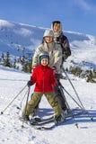 Leute der dreiköpfigen Familie lernen zusammen Ski fahren stockfotos