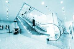 Leute an der Flughafenrolltreppe Stockbild