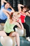 Leute in der Gymnastik auf Übungskugel Stockbild