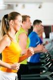Leute in der Gymnastik auf Tretmühlebetrieb Lizenzfreies Stockfoto
