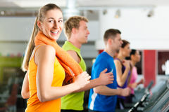 Leute in der Gymnastik auf Tretmühlebetrieb Lizenzfreie Stockbilder