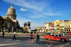 Leute in der Mitte von Havana mit dem Capitolio als Hintergrund Lizenzfreie Stockbilder