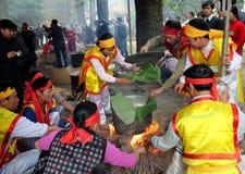 Leute in der traditionellen Kostümprüfung, zum des quadratischen Klebreises zu machen Stockbilder