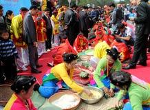 Leute in der traditionellen Kostümprüfung, zum des quadratischen Klebreises zu machen Stockbild