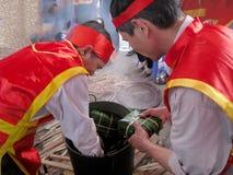 Leute in der traditionellen Kostümprüfung, zum des quadratischen Klebreises zu machen Lizenzfreies Stockfoto