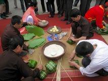 Leute in der traditionellen Kostümprüfung, zum des quadratischen Klebreises zu machen Lizenzfreie Stockfotos