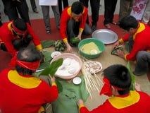 Leute in der traditionellen Kostümprüfung, zum des quadratischen Klebreises zu machen Lizenzfreie Stockbilder