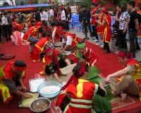 Leute in der traditionellen Kostümprüfung, zum des quadratischen Klebreises zu machen Stockfoto