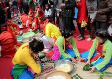 Leute in der traditionellen Kostümprüfung, zum des quadratischen Klebreises zu machen Stockfotos