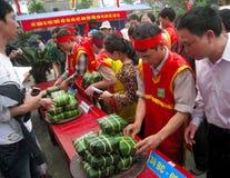 Leute in der traditionellen Kostümprüfung, zum des quadratischen Klebreises zu machen Lizenzfreies Stockbild