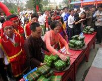 Leute in der traditionellen Kostümprüfung, zum des quadratischen Klebreises zu machen Stockfotografie