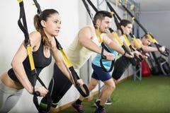 Leute an der Turnhalle, die trx Übungen tut Stockbilder