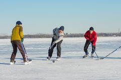 Leute des unterschiedlichen Alters, das Hockey auf einem gefrorenen Fluss Dnepr in Ukraine spielt Stockfoto