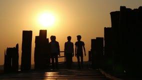 Leute, die über Holzbrücke bei Sonnenuntergang 1 gehen stock footage