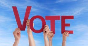 Leute, die Abstimmung im Himmel halten Stockfotografie