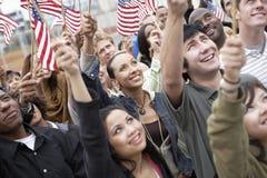 Leute, die amerikanische Flaggen halten Stockbild