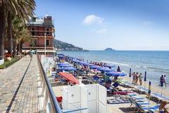 Leute, die auf Alassio-Strand in Italien ein Sonnenbad nehmen Stockbild