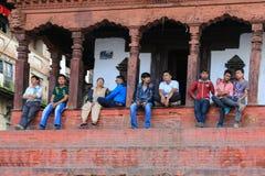 Leute, die auf dem Schritt in durbar Quadrat Kathmandus sitzen Stockfotografie