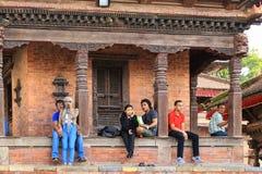 Leute, die auf dem Schritt in durbar Quadrat Kathmandus sitzen Stockbild